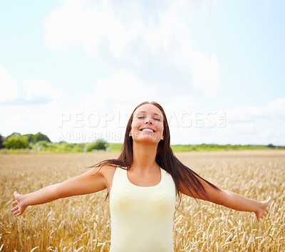 Buy stock photo Beautiful woman in a summer wheat field with her arms spread and eyes closed smiling - copyspace