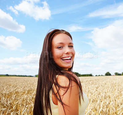 Buy stock photo Pretty young female smiling while walking in a summer wheat field - copyspace