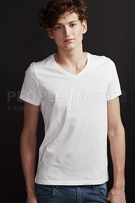 Buy stock photo A handsome young man smiling at you while posing in studio