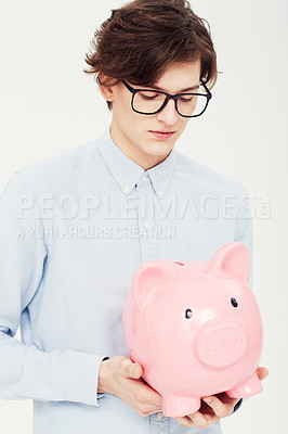 Buy stock photo A handsome young man looking into his piggy bank with cautious optimism