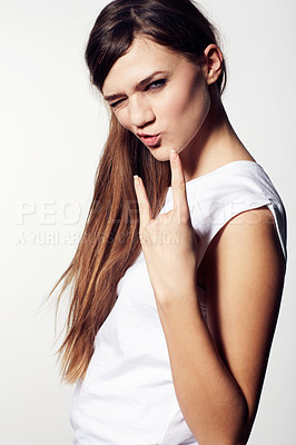 Buy stock photo A funky young beauty giving you devil horns and pouting with attitude