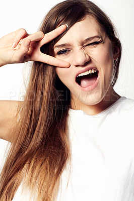 Buy stock photo A sassy young beauty winking at you with her fingers over her eyes