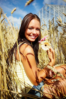 Buy stock photo Portrait of a happy young female sitting in a crop field holding flower