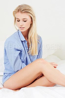 Buy stock photo A lovely young blonde woman sitting in bed with a blue shirt and bare legs looking downwards