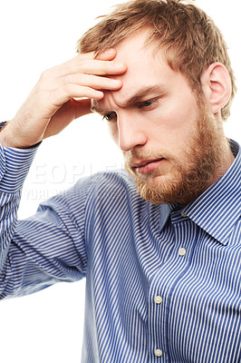 Buy stock photo A worried looking young man rubbing his forehead isolated on white