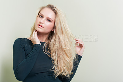 Buy stock photo A stunning young model pulling at her hair while posing alongside copyspace