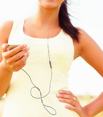 Buy stock photo Mid section image of a female listening to music, outdoors