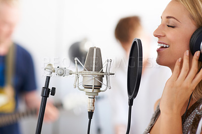 Buy stock photo Profile of a beautiful woman singing into a microphone with her two band members in the background