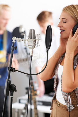 Buy stock photo A young woman singing into a microphone with a pop-shield with her band members in the background