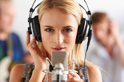 Buy stock photo A closeup of a beautiful woman singing into a microphone while wearing headphones