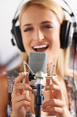 Buy stock photo A closeup of a beautiful blonde woman singing into a microphone while wearing headphones - portrait
