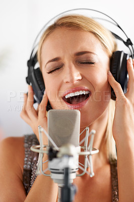 Buy stock photo A closeup of a beautiful blonde woman singing into a microphone while wearing headphones
