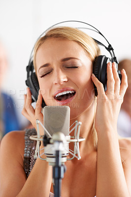 Buy stock photo A lovely young blonde woman singing into a microphone with her band members in the background