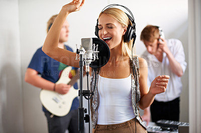 Buy stock photo A band of three young adults busy recording a track