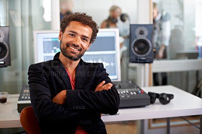 Buy stock photo A handsome music producer sitting with arms folded in his studio