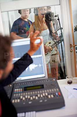 Buy stock photo A recording artist gesturing to a singer in an approving manner
