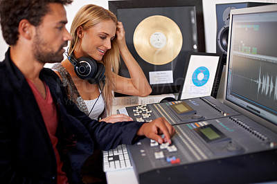Buy stock photo A young audio engineer  working on a mixing desk with his blonde colleague sitting next to him