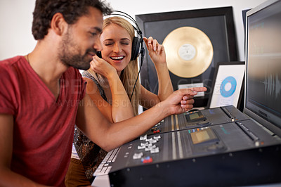 Buy stock photo Two young music producers working on their mixing desk with gold albums in the background