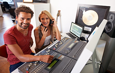 Buy stock photo Two audio engineers sitting in their recording studio smiling at the camera