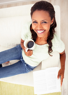 Buy stock photo Top view of a happy African American woman reading a book on the couch at tea time