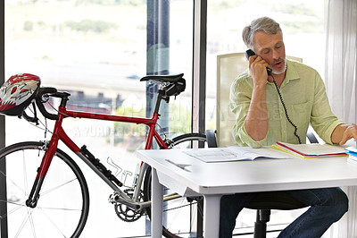 Buy stock photo Cropped shot of a mature businessman talking on his phone in the office