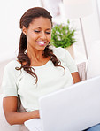 Pretty African American woman using a laptop at home