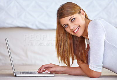 Buy stock photo Portrait of a pretty young woman lying on her bedroom floor using her laptop