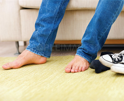 Buy stock photo Low section of young man's feet while sitting on the couch