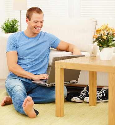 Buy stock photo Happy young guy sitting on the floor by the couch working on a laptop