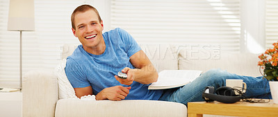 Buy stock photo Handsome guy holding a television remote control while relaxing on the couch