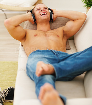 Buy stock photo Happy young guy enjoying music while relaxing on the sofa at home