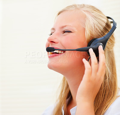 Buy stock photo Happy young business woman working on a headset, enjoying the conversation