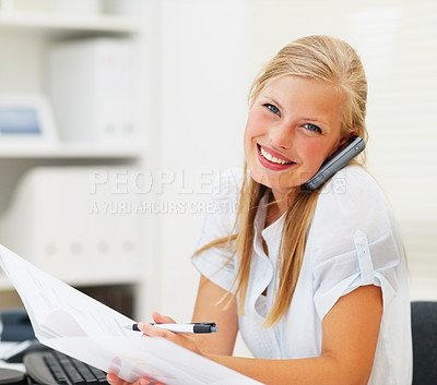 Buy stock photo Portrait of a business woman going through a document at work, speaking on the cellphone