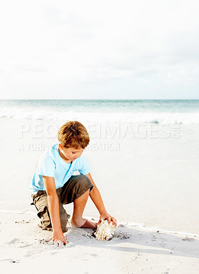 Buy stock photo Cute little children playing with a conch shell at the sea shore