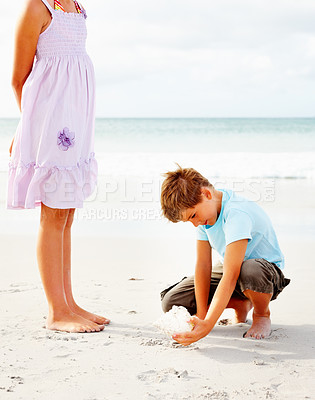 Buy stock photo Brother and sister at the sea shore, boy playing with a sea shell