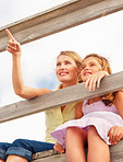 Upward view of a pretty woman sitting with daughter by a wooden railing