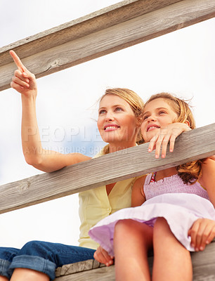 Buy stock photo Upward view of a cute woman pointing away sitting with daughter by a wooden railing