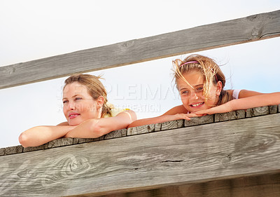 Buy stock photo Upward view of a mother and daughter lying on a bridge at the beach