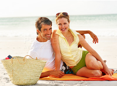 Buy stock photo Portrait of cute young couple sitting on the sea shore enjoying themselves