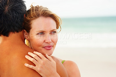 Buy stock photo Cute young woman embracing her husband while at the sea shore