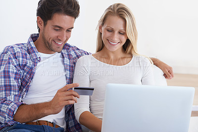 Buy stock photo A smiling young couple sitting on a couch and using a laptop and credit card to buy something online