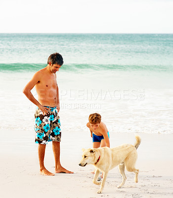 Buy stock photo Mature man and his son at the sea shore playing with a dog