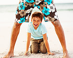 Happy little boy playing having fun with his father at the beach
