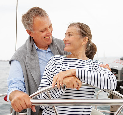 Buy stock photo Happy retired couple steering a boat on their voyage
