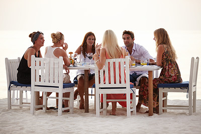 Buy stock photo A group of friends having dinner on the beach in the Maldives
