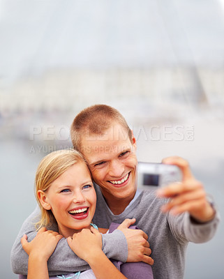 Buy stock photo Happy young couple holding a camera in front, self photography