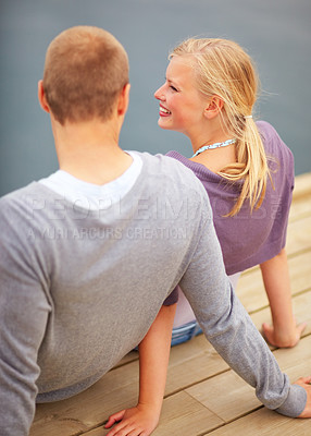 Buy stock photo Rear view of a happy young couple sitting at the edge of a wooden boardwalk