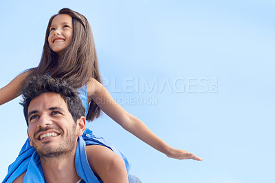 Buy stock photo Low angle shot of a girl sitting on her father's shoulders against a blue sky