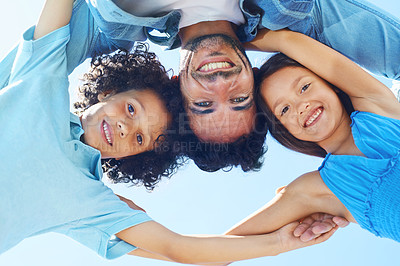 Buy stock photo Low angle portrait of a family standing arm in arm and looking down at the camera
