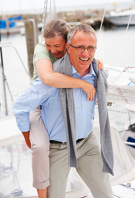 Buy stock photo Happy elderly couple in a playful mood while on a sailboat